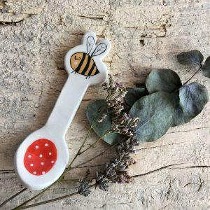 cucchiaino in ceramica con piccola ape accanto a ramoscello