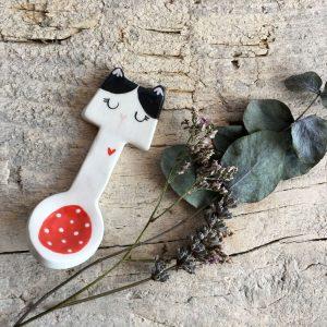 cucchiaino a forma di gatto bianco e nero accanto a un rametto