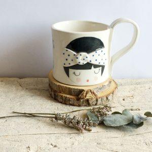 tazza da tè con decorata faccina con fascia turbante a pois blu tra i capelli