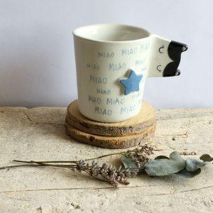 una tazza con manico a forma di muso di gatto bianco e nero, scritta miao e stella azzurra a rilievo sul davanti