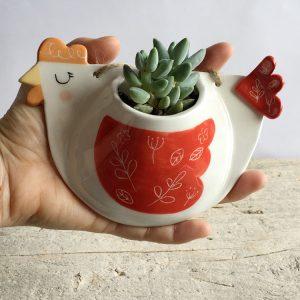 Io che tengo in mano un vaso di ceramica a forma di gallina