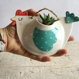 Io che tengo in mano un vaso di ceramica a forma di gallinella con finitura bianca e verde a pois