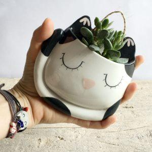 Io che tengo in mano un vaso di ceramica a forma di gatto bianco e nero