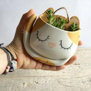 Io che tengo in mano un vaso di ceramica a forma di gatto bianco e rosso
