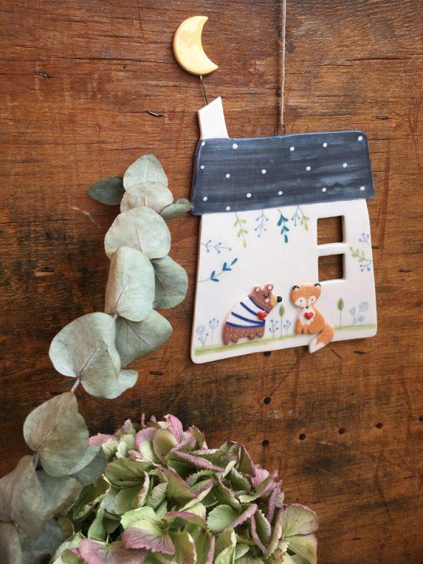 una decorazione da parete con orso volpe e luna che spunta dal tetto