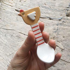 Io che tengo in mano un cucchiaino a forma di gallinella con finitura a righe rosse