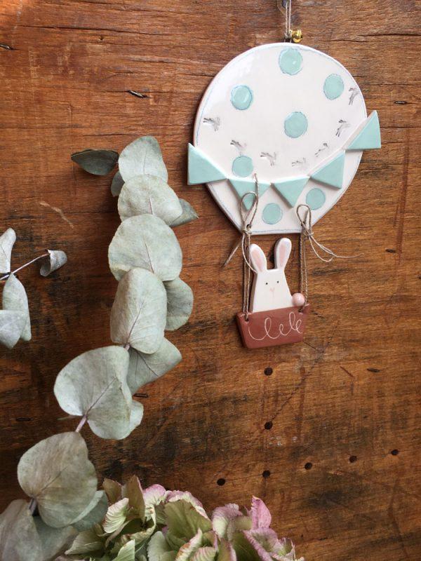 una decorazione da parete a forma di mongolfiera con coniglietto