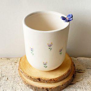 tazza con farfalla blu e fiori decorati lilla